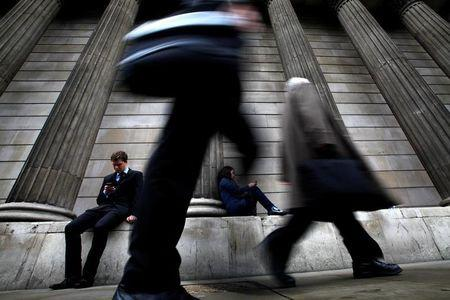 A man and woman use their mobile phones as commuters walk past the columns of the Bank of England in the City of London