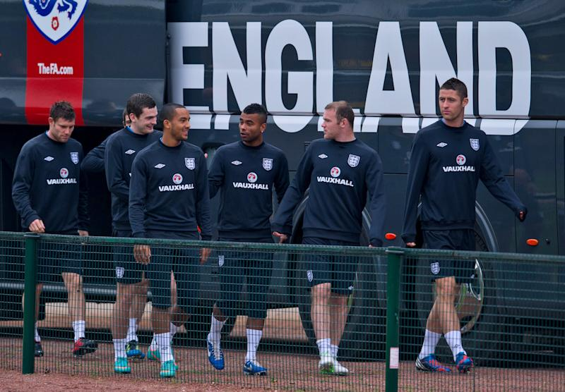 England's Ashley Cole, 3rd right, shares a joke with Theo Walcott, 4th left,  during a team training session, London Colney, Thursday Oct. 11, 2012. England will play against San Marino in a World Cup qualifying soccer match on Friday. (AP Photo/Tom Hevezi)