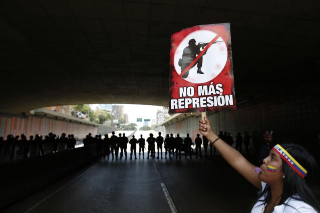 "Anti-government protester holds a placard reading:""stop repression"" in front of police during a march in Caracas March 8, 2014. Latin American foreign ministers will meet next week to discuss the unrest in Venezuela that has left at least 20 dead and convulsed the South American OPEC nation, diplomatic sources said on Friday. REUTERS/Carlos Garcia Rawlins (VENEZUELA - Tags: POLITICS CIVIL UNREST)"