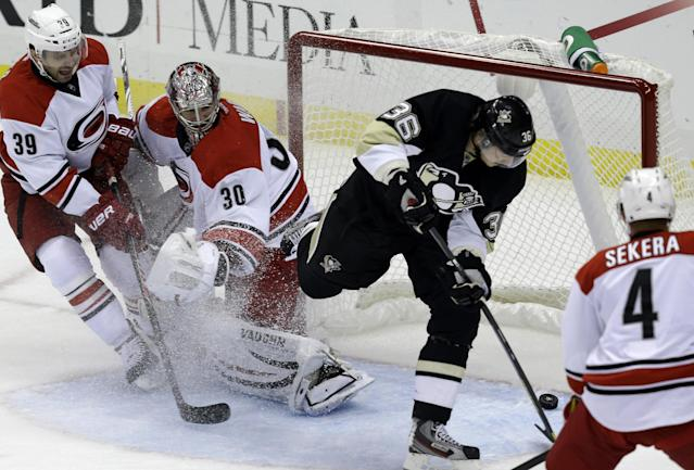 Pittsburgh Penguins' Jussi Jokinen (36) backhands the puck behind Carolina Hurricanes goalie Cam Ward (30) and Patrick Dwyer (39) for a first-period goal during an NHL hockey game in Pittsburgh, Tuesday, Oct. 8, 2013. (AP Photo/Gene J. Puskar)
