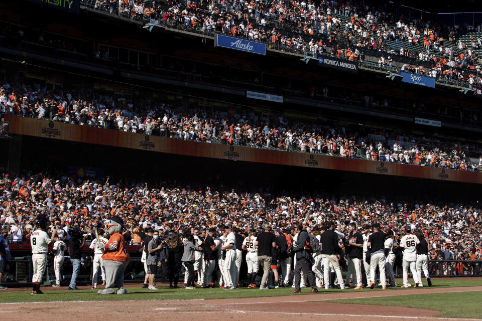 The San Francisco Giants celebrate after defeating the San Diego Padres in a baseball game in San Francisco, Sunday, Oct. 3, 2021. (AP Photo/John Hefti)