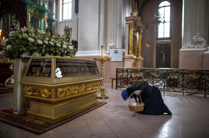 A Lithuanian Orthodox believer wearing a face mask to protect against the coronavirus, prays after a cake and Easter egg blessing ceremony at the Orthodox Church of the Holy Spirit in Vilnius, Lithuania, Saturday, April 18, 2020. For Orthodox Christians, this is normally a time of reflection, communal mourning and joyful release, of centuries-old ceremonies steeped in symbolism and tradition. But this year, Easter - by far the most significant religious holiday for the world's roughly 300 million Orthodox - has essentially been cancelled due to the COVID-19 pandemic. (AP Photo/Mindaugas Kulbis)