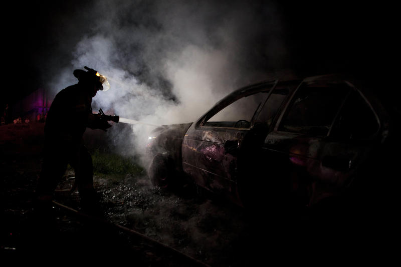 In this Sept. 18, 2012 photo, a firefighter puts out a smoldering car allegedly used in a robbery at a Coca-Cola distribution center in Morelia, Mexico. The robbers pistol-whipped three security guards, grabbed thousands of pesos in cash and fled. n cities and towns across Mexico, a nearly six-year offensive against drug cartels has been accompanied by a surge in common crime: assaults and robberies that grab no headlines but make life miserable for ordinary citizens.  (AP Photo/Alexandre Meneghini)