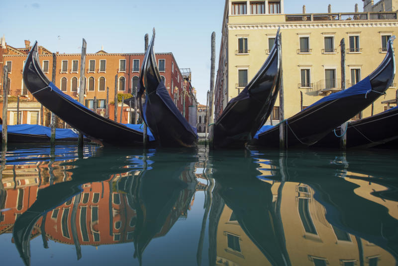 FILE - In this Monday, April 6, 2020 file photo, moored gondolas are reflected on the water of the Gran Canal, in Venice. The European Union announced Tuesday, June 30, 2020 that it will reopen its borders to travelers from 14 countries, but most Americans have been refused entry for at least another two weeks due to soaring coronavirus infections in the U.S. (AP Photo/Andrew Medichini, File)