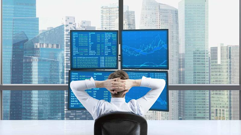 Broker trading shares relaxing looking at screen