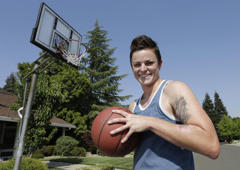 Holly Peterson, who plays professional women's tackle football for the Sacramento Sirens, holds a basketball in Elk Grove, Calif. on Friday, May 3, 2013. Peterson, who played college basketball at the University of California, Riverside, came out as a lesbian at age 15, when she was playing high school basketball. (AP Photo/Rich Pedroncelli)