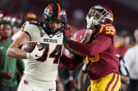 Oregon State tight end Teagan Quitoriano (84) stiff-arms Southern California linebacker Drake Jackson (99) after a reception during the second half of an NCAA college football game Saturday, Sept. 25, 2021, in Los Angeles. (AP Photo/Marcio Jose Sanchez)