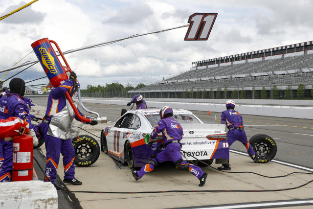 The crew refuels and changes tires for Denny Hamlin during a pit stop in the NASCAR Cup Series auto race at Pocono Raceway, Saturday, June 27, 2020, in Long Pond, Pa. (AP Photo/Matt Slocum)