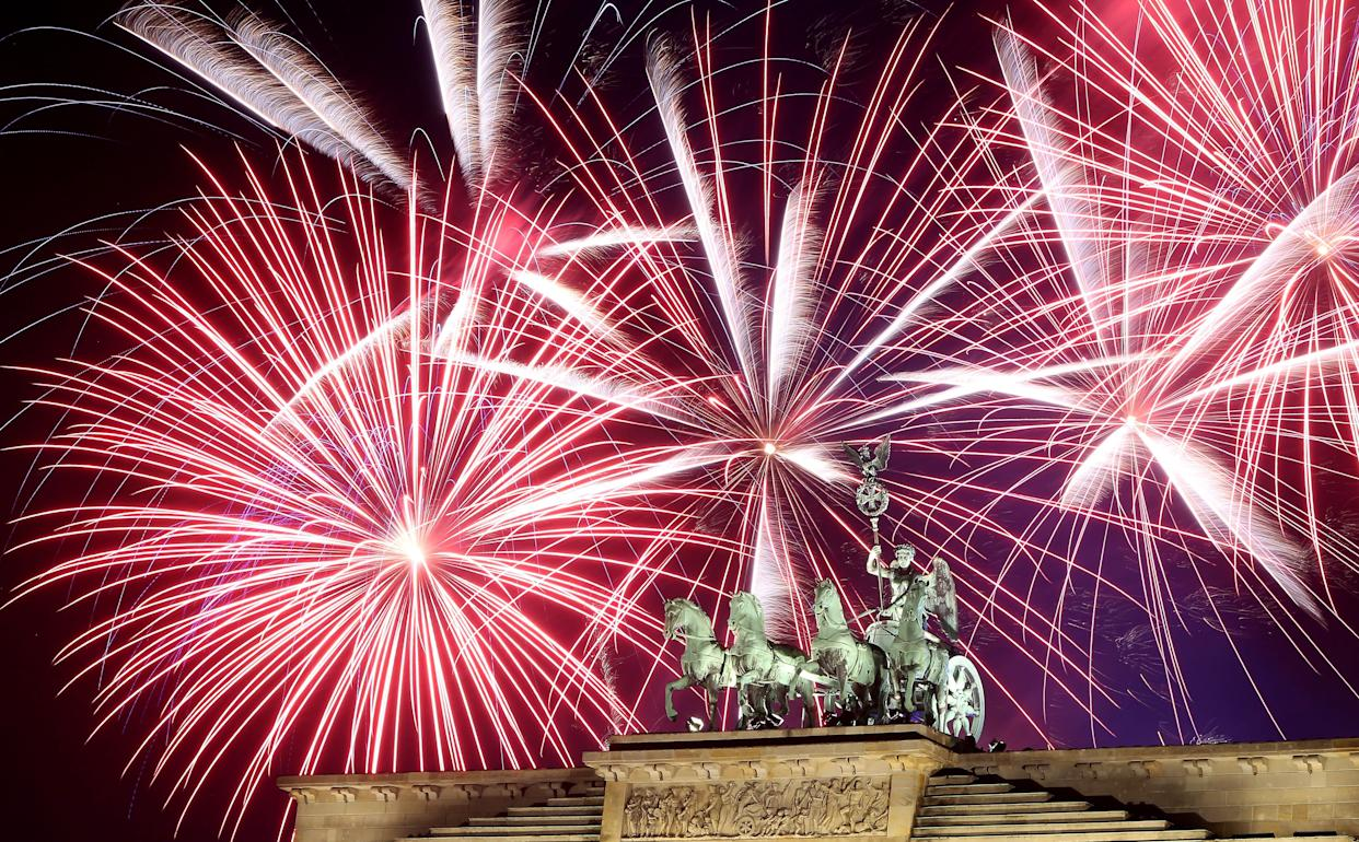 Fireworks explode over the Brandenburg Gate during New Year's festivities on January 1, 2018 in Berlin, Germany. (Photo: Adam Berry via Getty Images)