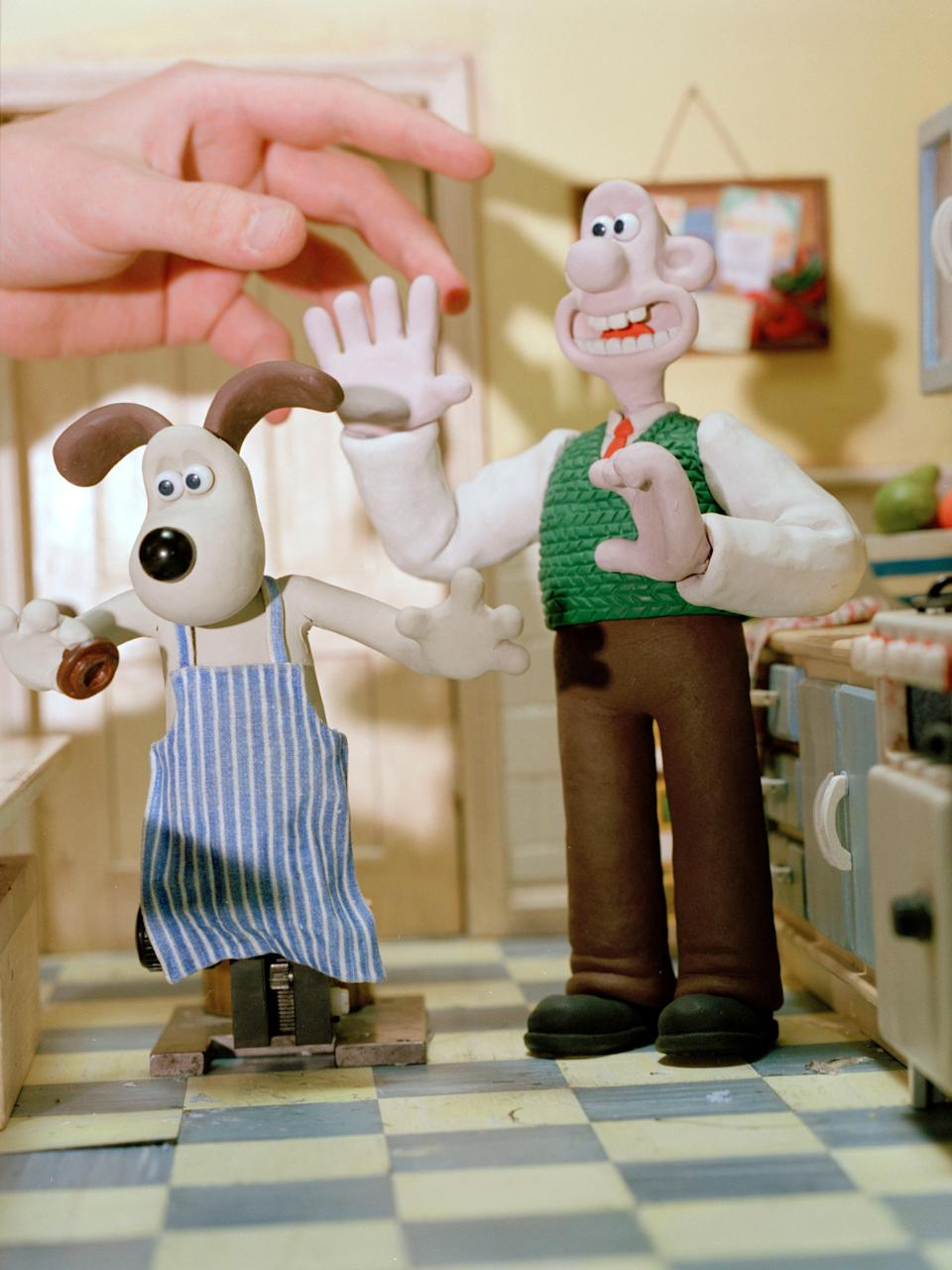 Wallace and Gromit on the 'Breakfast Set' with the hand of an animator. Nick Park's sets recreate the world of Wallace and Gromit in painstaking detail. Even the lettering, for example on a post box that will not be seen on the film will be drawn in. Created as part (all) of his degree and consuming seven years of his life before its completion 'A Grand day out', the original Wallace and Gromit production, gives some indication of the passion Nick Park has for his two-plasticene creations. The budget for that movie was ��11 000, with the star Peter Sallis offered ��50 to do the voice of Wallace, but even now, two Oscars later, with a team of 240 animators and a thirty million budget Park is still as close as ever to his animated friends, referring to them as his babies and claiming he would be happy if all he ever did was Wallace and Gromit. (Photo by In Pictures Ltd./Corbis via Getty Images)