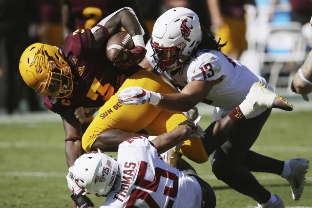 Arizona State running back Eno Benjamin (3) is brought down by Washington State linebacker Jahad Woods (13) and safety Skyler Thomas (25) during the first half of an NCAA college football game Saturday, Oct. 12, 2019, in Tempe, Ariz. (AP Photo/Ross D. Franklin)