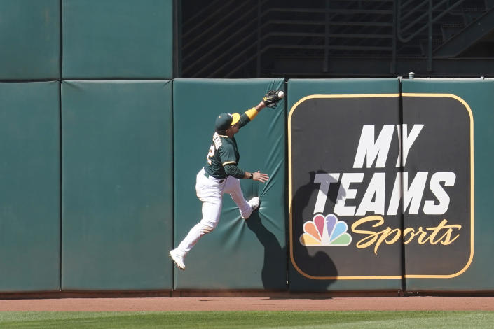 Oakland Athletics center fielder Ramon Laureano catches a fly ball during the eighth inning of a baseball game in Oakland, Calif., Sunday, May 2, 2021. (AP Photo/Jeff Chiu)