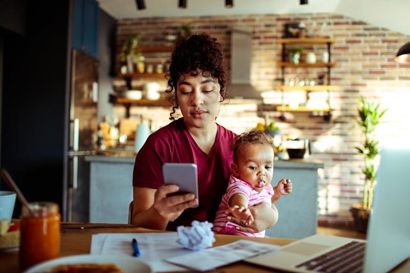 Close up of a mother using a phone with her daughter while having breakfast and doing bills