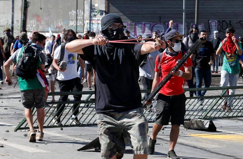 A demonstrator uses a slingshot during a protest against Chile's government in Valparaiso, Chile on Oct. 28, 2019. (Photo: Rodrigo Garrido/Reuters)