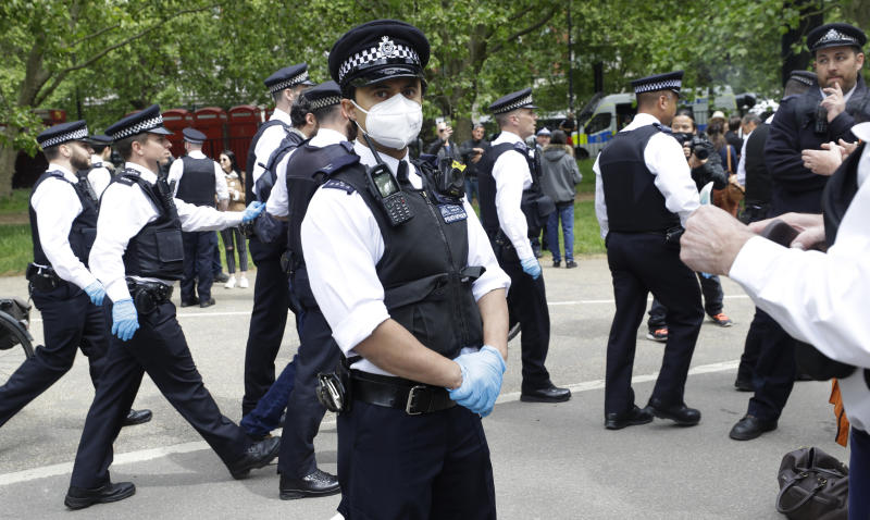 A police officer wears a face mask during a mass gathering protest organised by the group called 'UK Freedom Movement', in Hyde Park in London as the country is in lockdown to help stop the spread of coronavirus, Saturday, May 16, 2020. The group claims that the coronavirus lockdown is illegal. (AP Photo/Kirsty Wigglesworth)