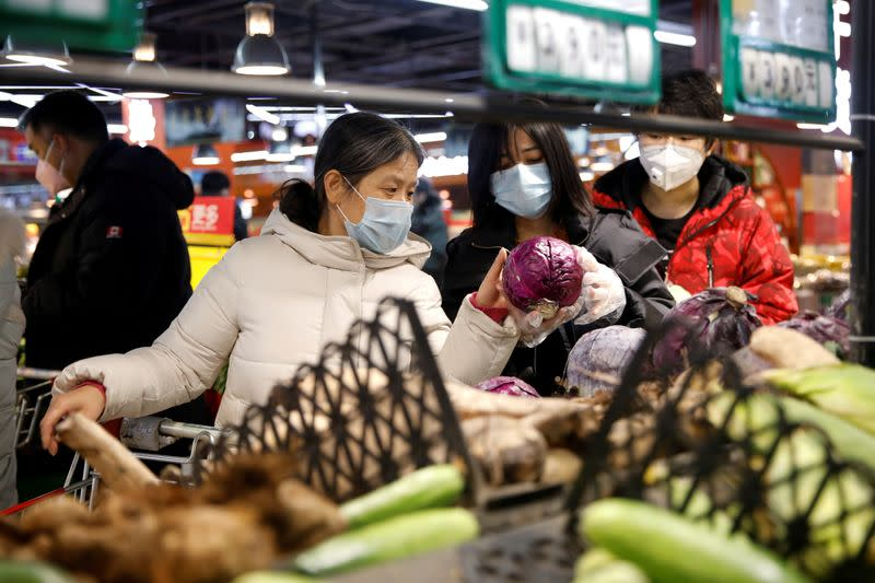 FILE PHOTO: People wearing face masks look for products at a supermarket in Beijing
