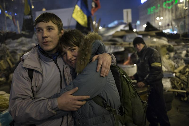 "A young couple embrace each other as they look at the stage during a concert after a pro-European Union rally in the Independence Square in Kiev, Ukraine, Wednesday, Dec. 18, 2013. Putin and Yanukovych both pledged Tuesday, Dec. 17, 2013 to boost economic and trade ties to expand the ""strategic partnership"" between the two neighbors. (AP Photo/Alexander Zemlianichenko)"