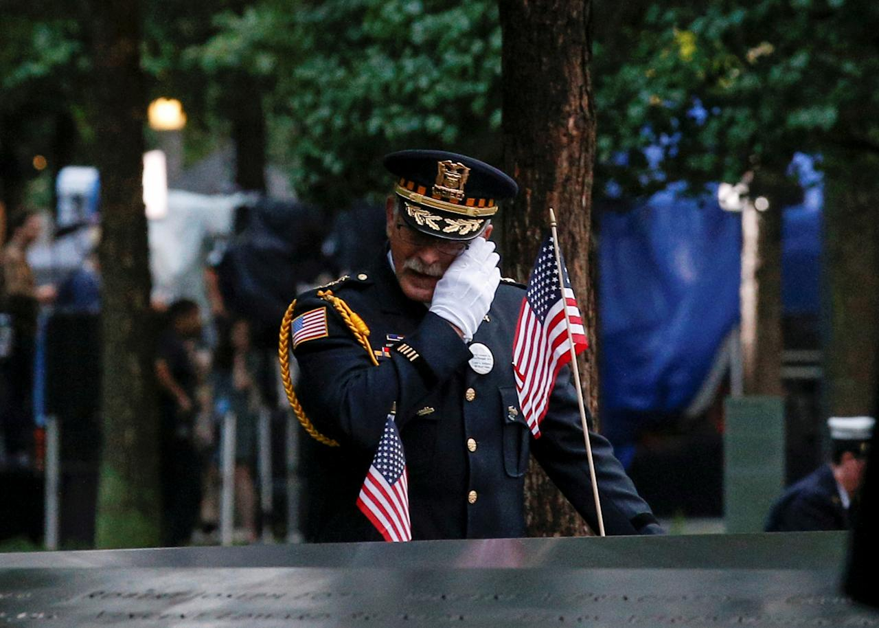 A guest wipes a tear among names at the edge of the south reflecting pool at the National 9/11 Memorial and Museum during ceremonies marking the 17th anniversary of the
