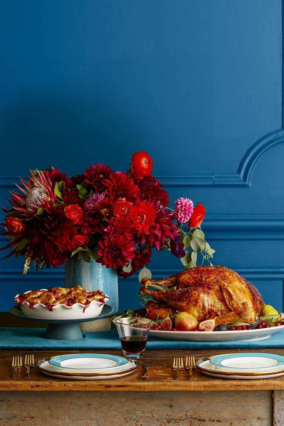 "<p>With this striking arrangement of dahlias, roses, and ranunculus, the <a href=""https://www.goodhousekeeping.com/holidays/thanksgiving-ideas/g112/cranberry-sauce-recipes/"" rel=""nofollow noopener"" target=""_blank"" data-ylk=""slk:cranberry sauce"" class=""link rapid-noclick-resp"">cranberry sauce</a> won't be the most colorful part of your Thanksgiving spread. Place all of them in a complementary vase for an added pop of color. </p>"