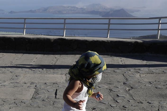 A boy wears a face mask as he plays with Taal volcano in the rear from Tagaytay, Cavite province, southern Philippines on Thursday Jan. 16, 2020. Taal volcano belched smaller plumes of ash Thursday but shuddered continuously with earthquakes and cracked roads in nearby towns, which were blockaded by police due to fears of a bigger eruption. (AP Photo/Aaron Favila)
