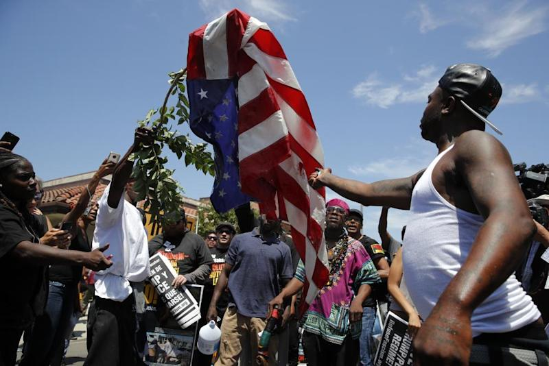 Counter-protesters burn an American flag.