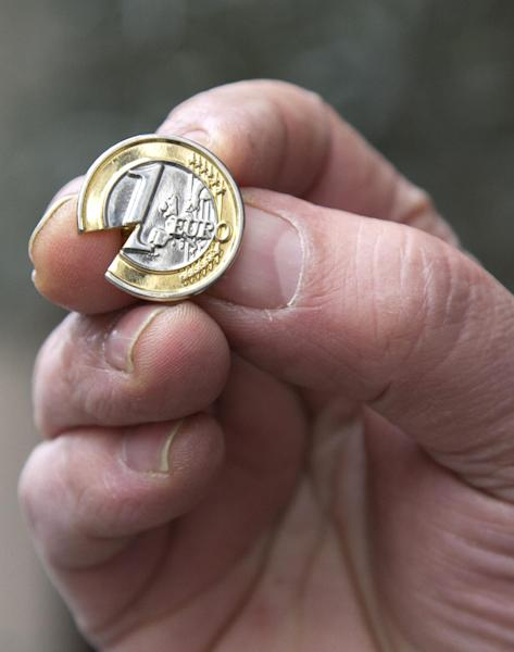 A Cypriot man, who did not wish to be identified, holds up a souvenir Cypriot euro coin lapel pin with a piece taken out near the Cypriot delegation building in Brussels on Sunday, March 24, 2013. The EU says a top official will chair a high-level meeting on Cyprus in a last-ditch effort to seal a deal before finance ministers decide whether the island nation gets a 10 billion euro bailout loan to save it from bankruptcy. (AP Photo/Virginia Mayo)