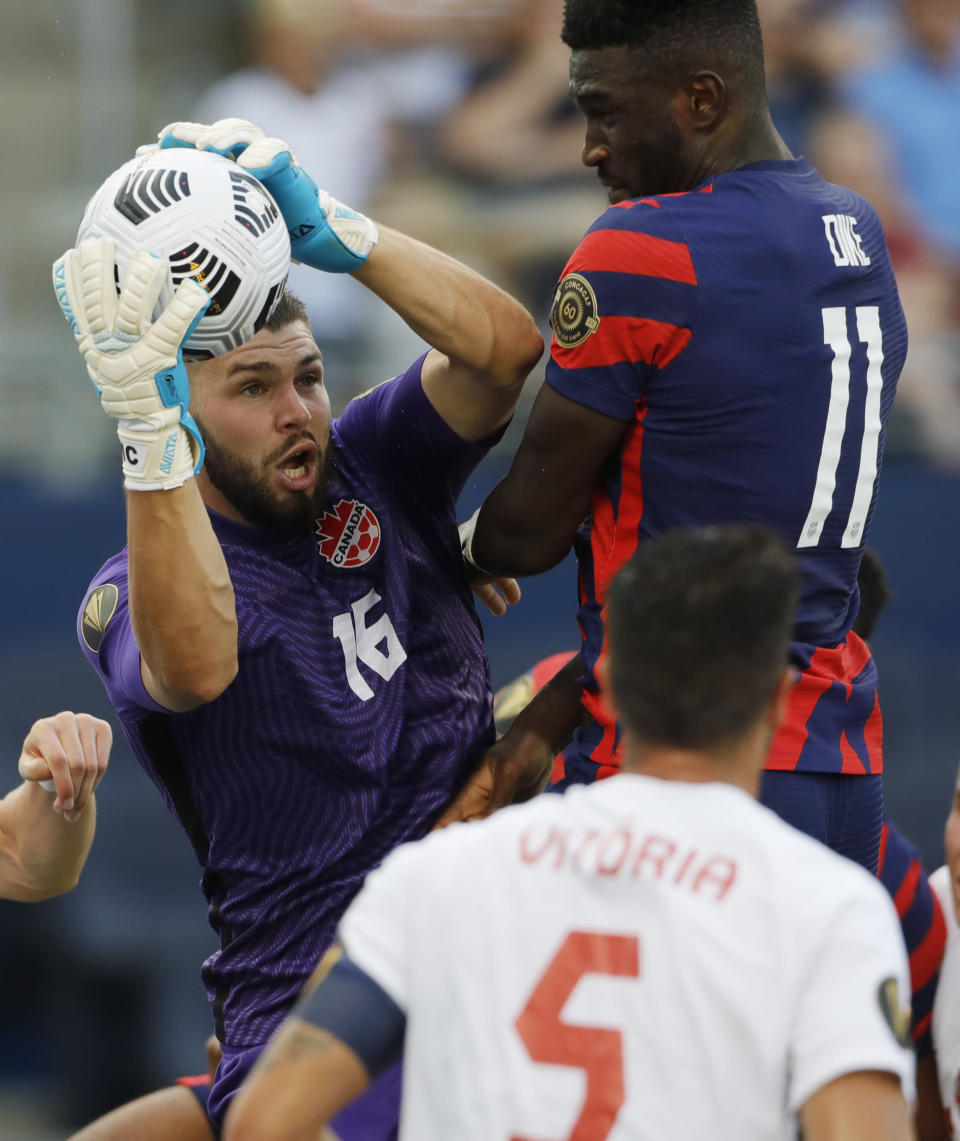 Canada goalkeeper Maxime Crepeau (16) grabs a corner kick away from U.S. forward Daryl Dike (11) during the second half of a CONCACAF Gold Cup soccer match in Kansas City, Kan., Sunday, July 18, 2021. (AP Photo/Colin E. Braley)