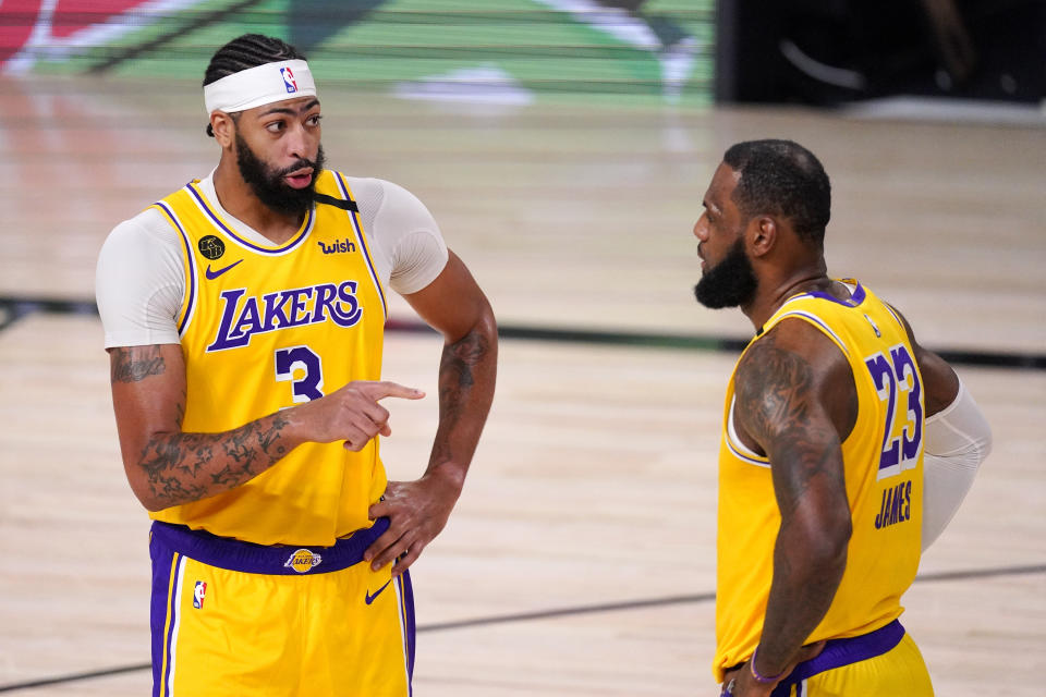 Los Angeles Lakers' Anthony Davis (3) talks with LeBron James (23) during the second half of an NBA conference final playoff basketball game against the Denver Nuggets Thursday, Sept. 24, 2020, in Lake Buena Vista, Fla. (AP Photo/Mark J. Terrill)