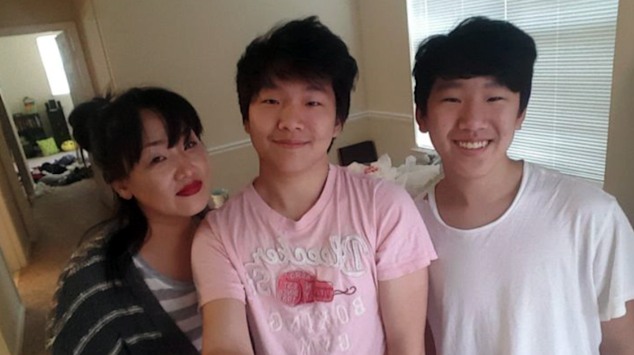 Hyun Jung Grant stands with her sons, Randy Park, center, and Eric Park, in this undated family photo.
