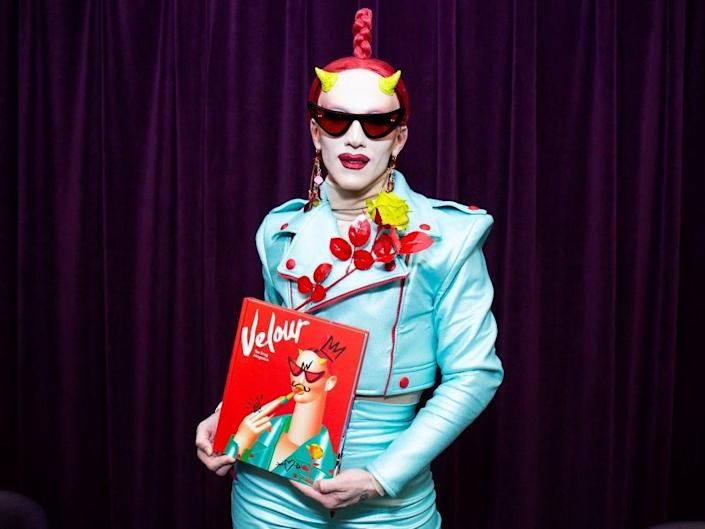 Sasha Velour RuPaul's Drag Race wearing blue suit and holding up a red book with her name and picture on it