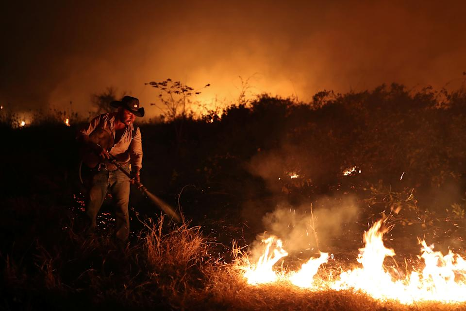"""Sebastiao Baldi Silva Junior, 40, who works on a farm, attempts to put out a fire on a ranch in the Pantanal, the world's largest wetland, in Pocone, Mato Grosso state, Brazil, August 26, 2020. REUTERS/Amanda Perobelli  TPX IMAGES OF THE DAY  SEARCH """"PANTANAL PEROBELLI"""" FOR THIS STORY. SEARCH """"WIDER IMAGE"""" FOR ALL STORIES"""