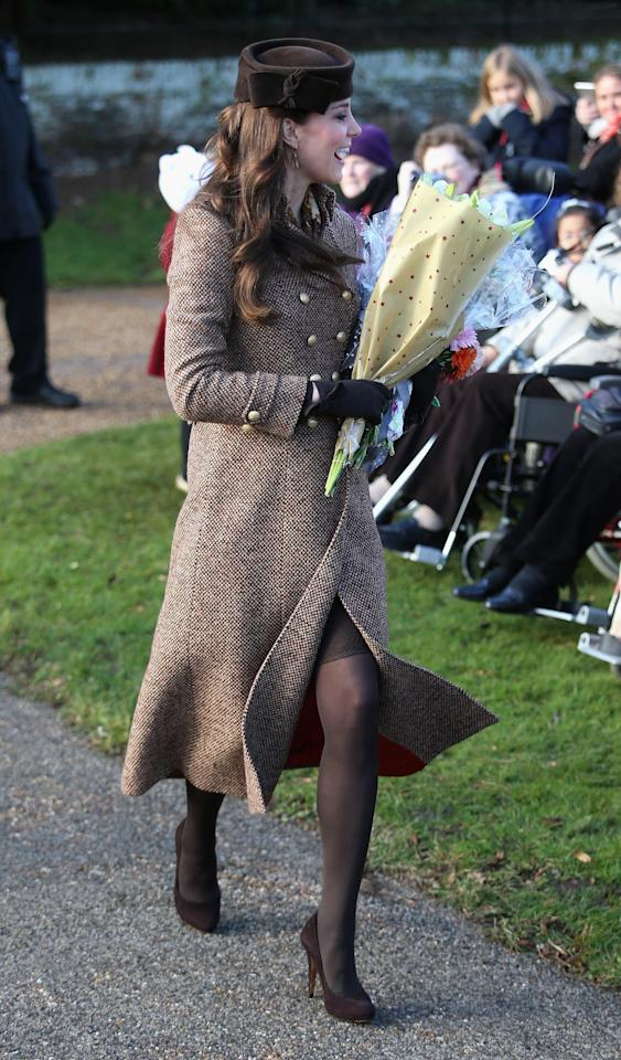 <p>Kate was pregnant with her second child Charlotte at the Christmas Day service in 2014. She wore Moloh's wool 'Turpin' coat over a brown animal print dress from Hobbs, with a printed Really Wild scarf. A matching Lock & Co hat and her suede Emmy 'Valerie' courts completed the look. (Getty) </p>