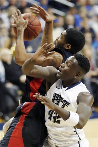 Delaware State's Kendall Gray, left, grabs a rebound in front of Pittsburgh's Talib Zanna (42) in the first half of their NCAA college basketball game, Wednesday, Dec. 19, 2012, in Pittsburgh. (AP Photo/Keith Srakocic)