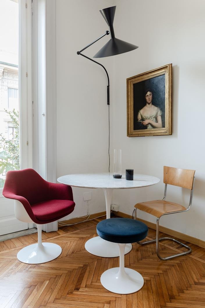 """<div class=""""caption""""> In the corner of the living room, Alex created an intimate dining space with a set of Eero Saarinen's iconic Tulip designs for Knoll including a <a href=""""https://fave.co/3k2FtZS"""" rel=""""nofollow noopener"""" target=""""_blank"""" data-ylk=""""slk:table"""" class=""""link rapid-noclick-resp"""">table</a>, <a href=""""https://fave.co/3fn16k6"""" rel=""""nofollow noopener"""" target=""""_blank"""" data-ylk=""""slk:armchair"""" class=""""link rapid-noclick-resp"""">armchair</a> and <a href=""""https://fave.co/319g1Jv"""" rel=""""nofollow noopener"""" target=""""_blank"""" data-ylk=""""slk:stool."""" class=""""link rapid-noclick-resp"""">stool.</a> A S43 chair by Mart Stam rounds out the bunch, while a <a href=""""https://nemolighting.com/product/lampe-de-marseille/"""" rel=""""nofollow noopener"""" target=""""_blank"""" data-ylk=""""slk:Marseilles Lamp by Le Corbusier"""" class=""""link rapid-noclick-resp"""">Marseilles Lamp by Le Corbusier</a> lights the nook. </div>"""