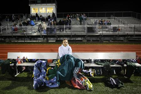Fifteen year-old Sarah Steenhuysen (C) watches her high school soccer teammates play a game against Bishop Feehan in Attleboro, Massachusetts October 25, 2013. REUTERS/Brian Snyder