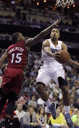 Miami Heat's Mario Chalmers (15) lets the Charlotte Bobcats' Gerald Henderson (9) slip by for a score during the first half of an NBA basketball game in Charlotte, N.C., Friday, April 5, 2013. (AP Photo/Bob Leverone)