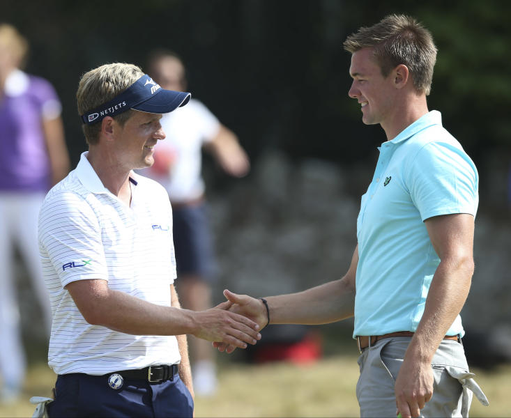 Luke Donald of England, left, shakes hands with Ben Stow of England after their practice round ahead of the British Open Golf Championship at Muirfield, Scotland, Tuesday July 16, 2013. (AP Photo/Scott Heppell)