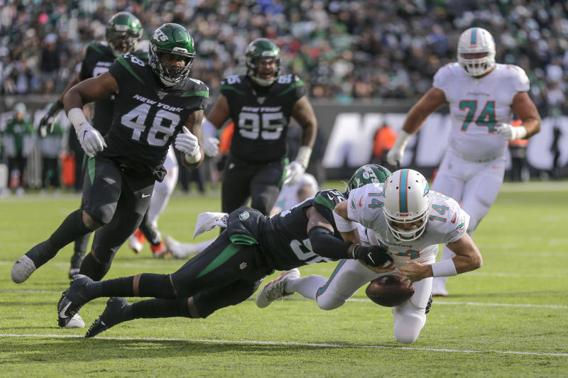 Miami Dolphins quarterback Ryan Fitzpatrick (14) fumbles the ball as he's hit by New York Jets defensive end John Franklin-Myers (56) during the first quarter of an NFL football game, Sunday, Dec. 8, 2019, in East Rutherford, N.J. Fitzpatrick recovered the ball on the play. (AP Photo/Seth Wenig)