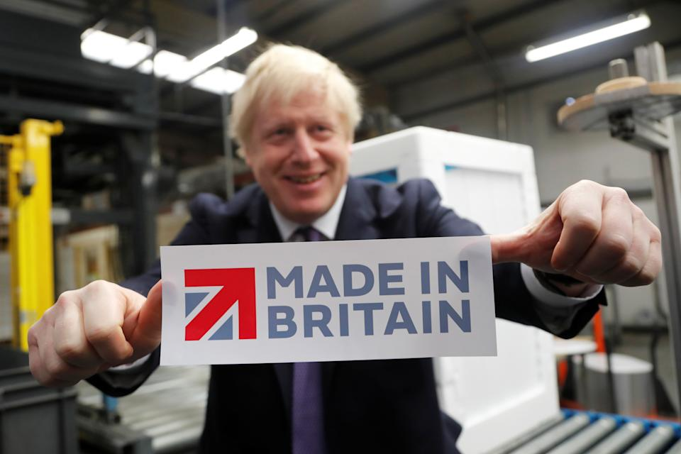 Britain's Prime Minister Boris Johnson holds a sign he took off the packaging of a washing machine at Ebac electrical appliances manufacturer during a General Election campaign trail stop in Newton Aycliffe, Britain November 20, 2019. Frank Augstein/Pool via REUTERS