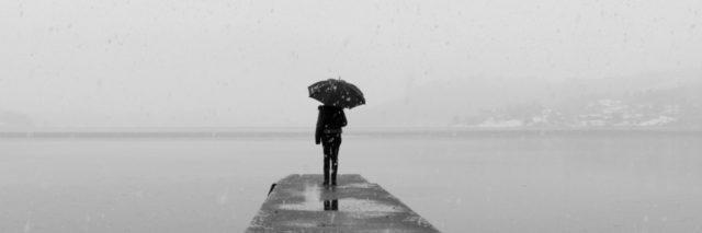 woman standing with umbrella at the end of a dock near the water.