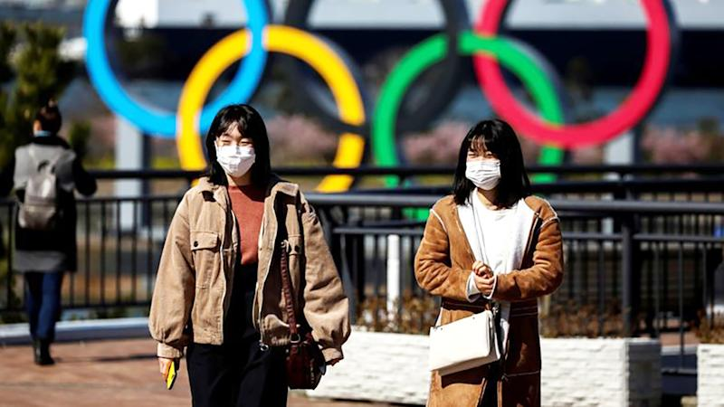 Two women, pictured here wearing face masks near the Olympic rings in Tokyo.