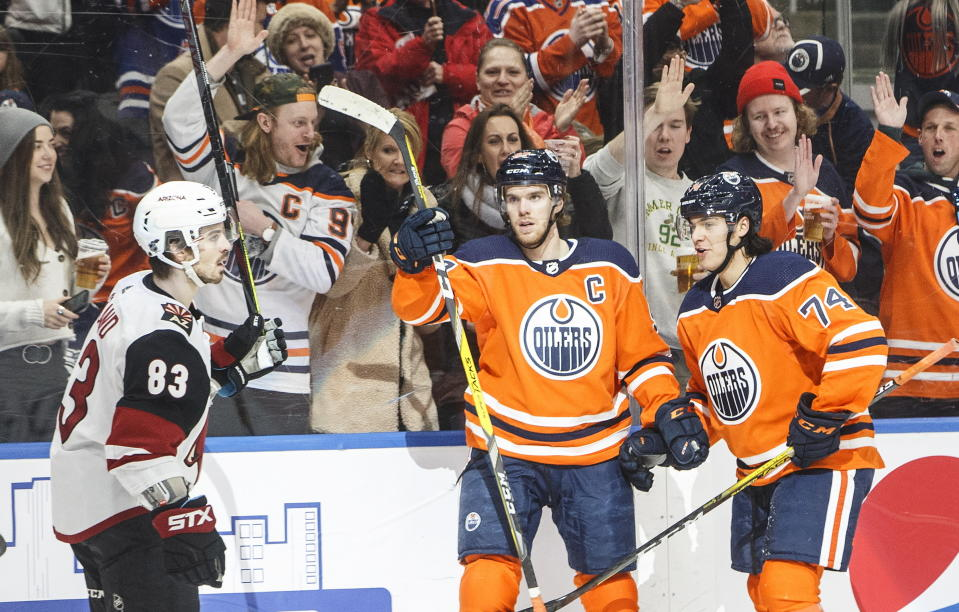 Arizona Coyotes' Conor Garland (83) skates past as Edmonton Oilers' Connor McDavid (97) and Ethan Bear (74) celebrate a goal during second period NHL action in Edmonton, Alberta, on Saturday, Jan. 18, 2020. (Jason Franson/The Canadian Press via AP)