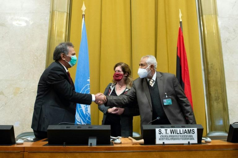 """The heads of the rival Libyan delegations shake hands in front of the UN envoy after agreeing to a """"permanent"""" ceasefire"""