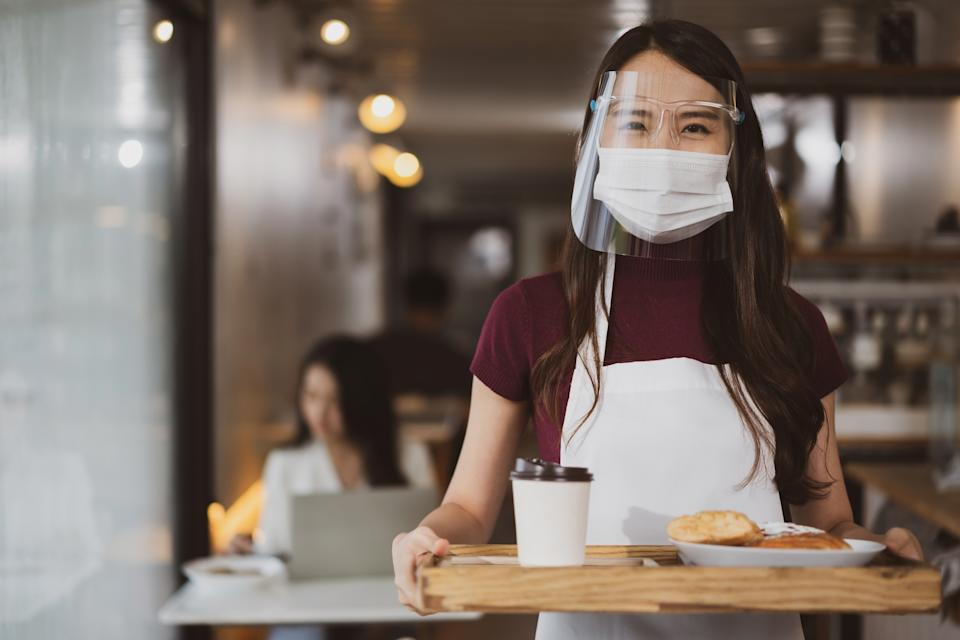 Asian waitress with face protective mask and face shield serving coffee and bread in coffee shop