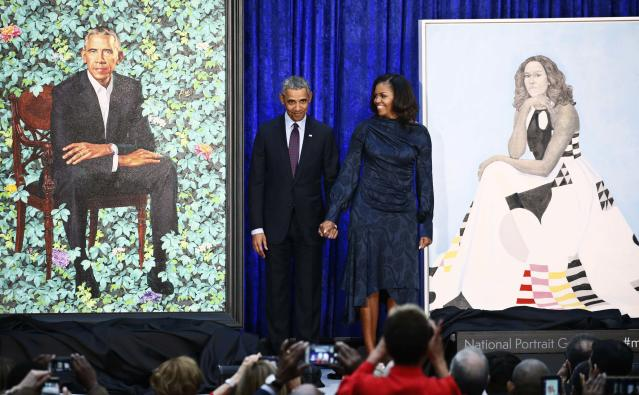 Former U.S. President Barack Obama and former first lady Michelle Obama hold hands between their portraits during an unveiling ceremony at the Smithsonian's National Portrait Gallery in Washington, U.S., February 12, 2018. REUTERS/Jim Bourg