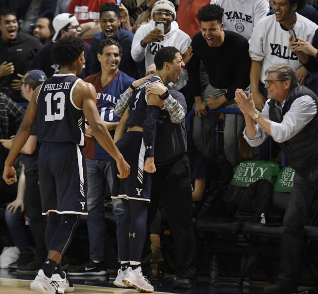 Yale's Alex Copeland, center, celebrates with fans as teammate Trey Phills, left, looks on in the final minute of an NCAA college basketball game for the Ivy League championship against Harvard at Yale University in New Haven, Conn., Sunday, March 17, 2019, in New Haven, Conn. (AP Photo/Jessica Hill)