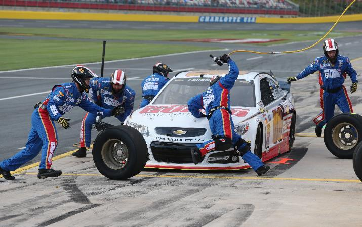 Crew members perform a pit stop on driver Dale Earnhardt Jr's car during qualifying for the NASCAR Sprint All-Star auto race at Charlotte Motor Speedway in Concord, N.C., Saturday, May 17, 2014. (AP Photo/Bob Jordan)