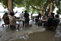 """Customers of the riverside Chaopraya Antique Café react to a passing boat's wake as they enjoy themselves in the extraordinary high water levels in the Chao Phraya River in Nonthaburi, near Bangkok, Thailand, Thursday, Oct. 7, 2021. The flood-hit restaurant has become an unlikely dining hotspot after fun-loving foodies began flocking to its water-logged deck to eat amid the lapping tide. Now, instead of empty chairs and vacant tables, the cafe is as full as ever, offering an experience the canny owner has re-branded as """"hot-pot surfing."""" (AP Photo/Sakchai Lalit)"""