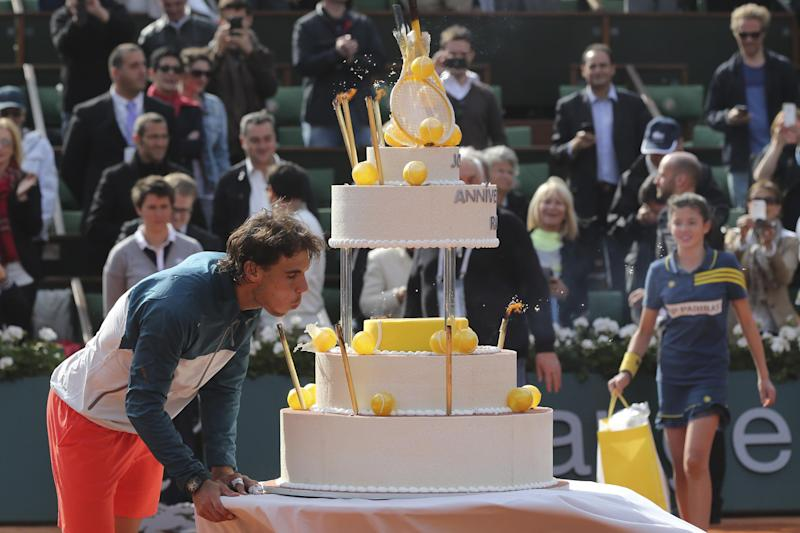 Spain's Rafael Nadal blows out the candles on his birthday cake as he celebrates his 27th birthday on center court after defeating Japan's Kei Nishikori in three sets 6-4, 6-1, 6-3, in their fourth round match at the French Open tennis tournament, at Roland Garros stadium in Paris, Monday June 3, 2013. (AP Photo/Michel Euler)