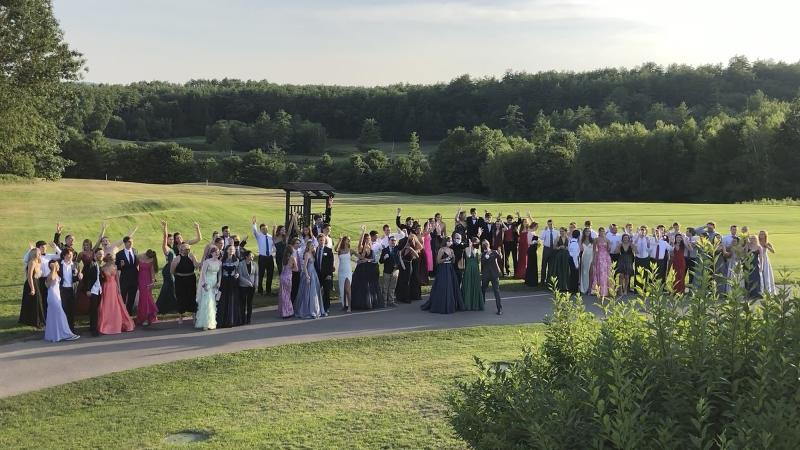 In this Saturday, July 18, 2020, image provided by Carol Justic, recent Bedford High School graduates and students pose for a photo at their outdoor prom outdoor at the Stonebridge Country Club in Goffstown, N.H., organized during the coronavirus pandemic. Amid the debate over how to reopen schools safely, some teens and parents are organizing private proms to replace events canceled because of the coronavirus. (Carol Justic via AP)